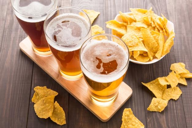 Variedade de copos de cerveja com chips de nachos em uma mesa de madeira
