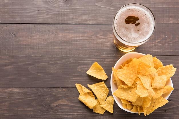 Variedade de copos de cerveja com chips de nachos em uma mesa de madeira.