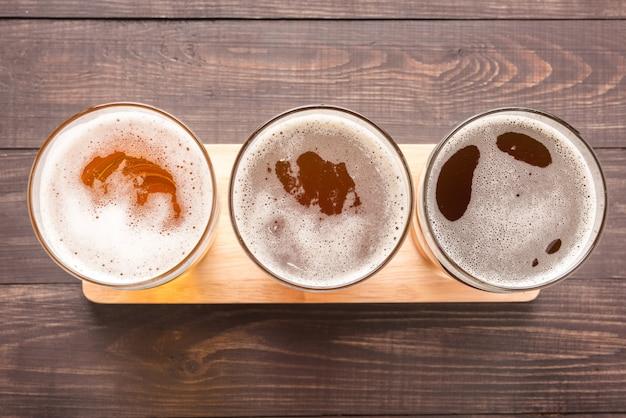 Variedade de copos de cerveja em uma mesa de madeira. vista do topo