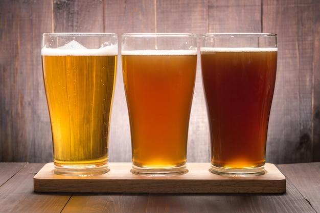 Variedade de copos de cerveja em uma mesa de madeira