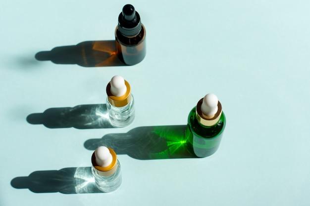 Variedade de cosméticos orgânicos com ingredientes de ervas. soro para cuidados com a pele. cosméticos naturais em frascos de vidro com uma pipeta de fundo azul.