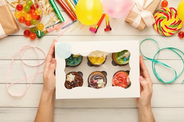 Variedade de cupcakes saborosos com tops coloridos de creme de manteiga em mãos femininas