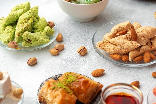 Variedade de delícias turcas com copo de chá no fundo cinza
