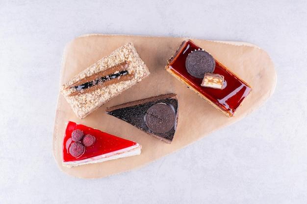 Variedade de deliciosos bolos na placa de madeira. foto de alta qualidade
