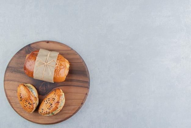 Variedade de deliciosos pastéis na placa de madeira.