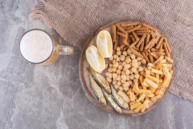 Variedade de deliciosos petiscos na peça de madeira com cerveja. foto de alta qualidade