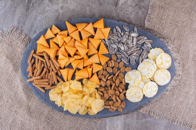 Variedade de deliciosos petiscos na peça de madeira. foto de alta qualidade