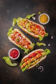 Variedade de diferentes cachorros-quentes caseiros com linguiça, cebola frita, tomate e feijão