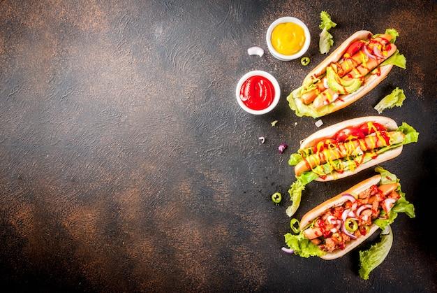 Variedade de diferentes cachorros-quentes caseiros com salsicha, cebola frita, tomate e feijão, vista superior copyspace enferrujado escuro