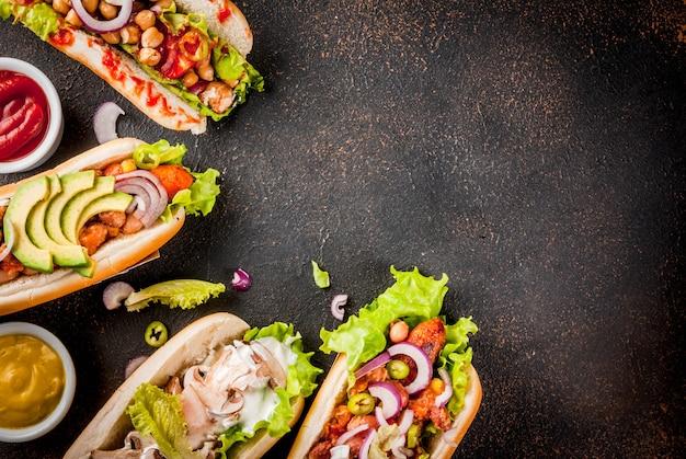 Variedade de diferentes cachorros-quentes caseiros de cenoura vegana, com cebola frita, abacate, pimentão, cogumelos, tomate e feijão, vista superior copyspace enferrujado escuro