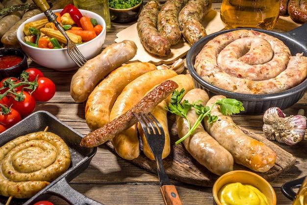 Variedade de diferentes enchidos fritos. conjunto com várias carnes da baviera, frankfurt, salsichas alemãs grelhadas, oktoberfest ou conceito de festa de churrasco de verão