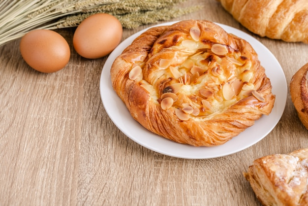 Variedade de diferentes pães frescos, bolos, croissants, trigos e ovos sobre a superfície da mesa de madeira.
