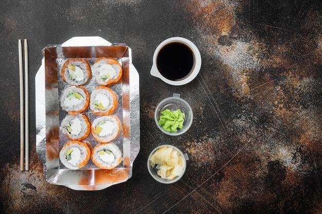 Variedade de diferentes sushis e pãezinhos de sal, salmão e atum em conjunto de conceito de delivery, em estilo rústico escuro antigo