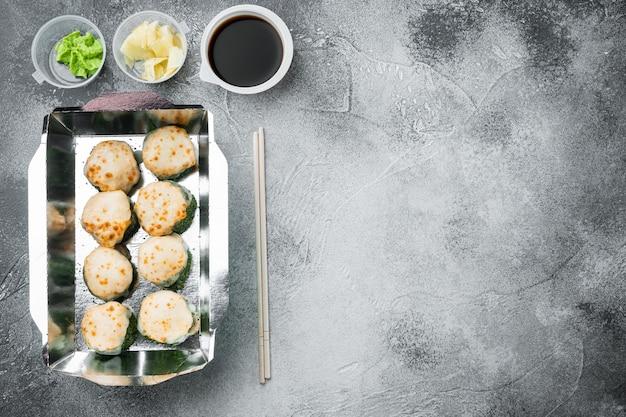 Variedade de diferentes sushis e pãezinhos de salmão e atum em conjunto de conceito de entrega de comida, na pedra cinza