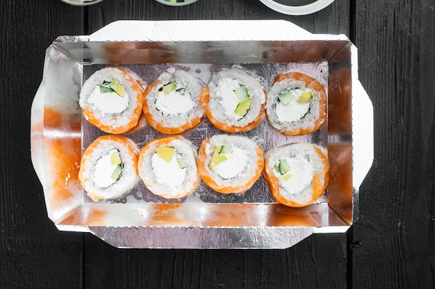 Variedade de diferentes sushis e pãezinhos, salmão e atum em conjunto de conceito de entrega de comida, na mesa de madeira preta