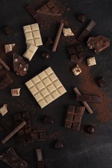 Variedade de diferentes tipos de barras de chocolate quebradas em pedaços