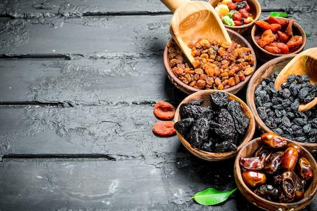 Variedade de diferentes tipos de frutas secas em tigelas. na mesa rústica preta.