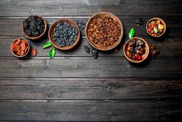 Variedade de diferentes tipos de frutas secas em tigelas. sobre um fundo de madeira.