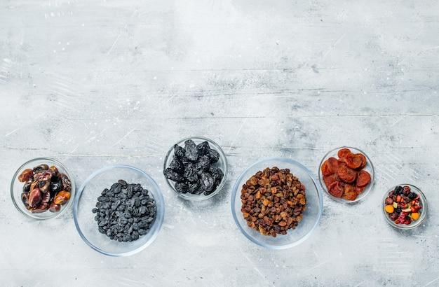 Variedade de diferentes tipos de frutas secas em tigelas. sobre um fundo rústico.