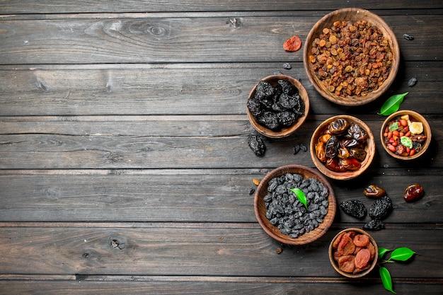 Variedade de diferentes tipos de frutas secas em tigelas sobre uma mesa de madeira.