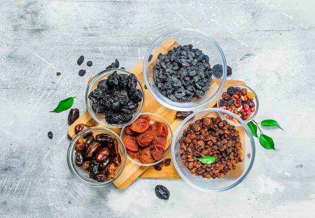 Variedade de diferentes tipos de frutas secas em tigelas. sobre uma mesa rústica.