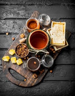 Variedade de diferentes tipos de mel. sobre fundo preto rústico.
