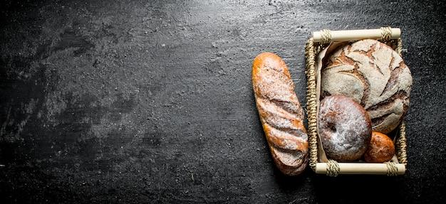 Variedade de diferentes tipos de pão na cesta. sobre fundo preto rústico