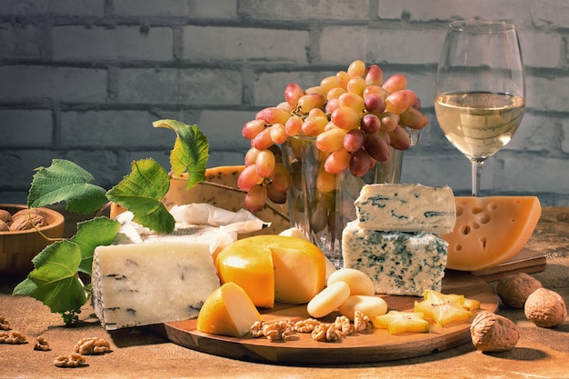 Variedade de diferentes tipos de queijo com copo de videira e uvas na mesa. fundo de queijo.