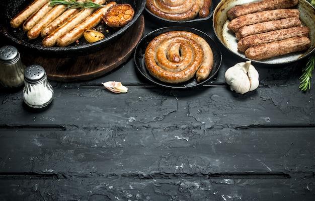 Variedade de diferentes tipos de salsichas fritas na mesa de madeira preta.
