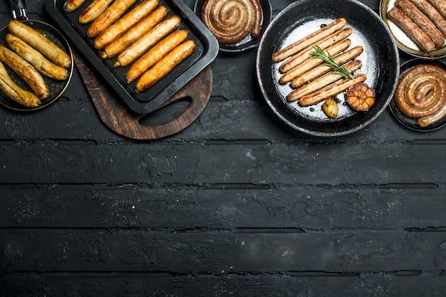 Variedade de diferentes tipos de salsichas fritas na mesa rústica preta.