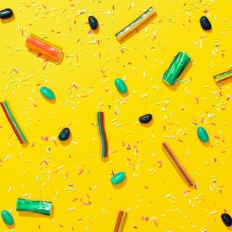 Variedade de doces coloridos diferentes em fundo amarelo