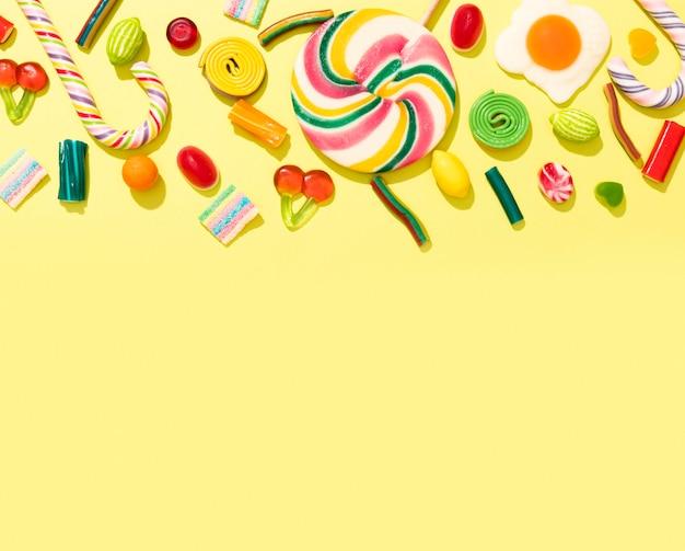 Variedade de doces coloridos sobre fundo amarelo, com espaço de cópia