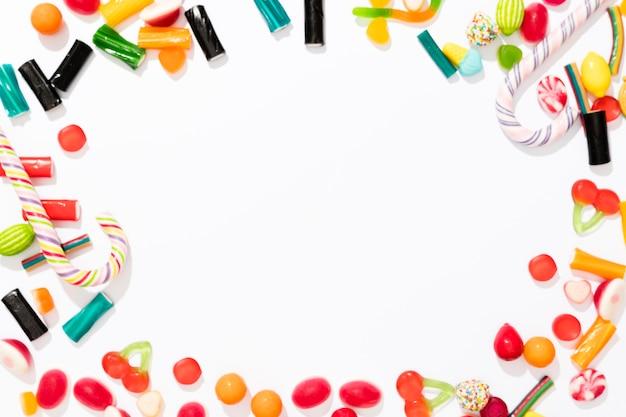 Variedade de doces coloridos sobre fundo branco, com espaço de cópia