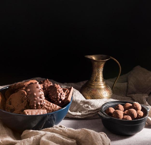 Variedade de doces de chocolate de alto ângulo em tigelas