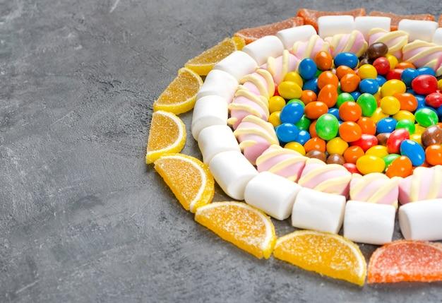 Variedade de doces e balas lindamente dispostos sobre a mesa. fundo com espaço de cópia.