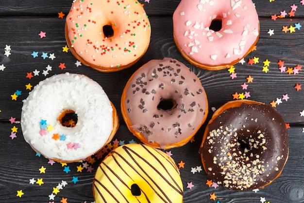 Variedade de donuts coloridos decorados com confetes coloridos granulado no escuro de madeira