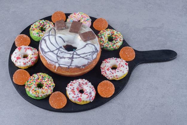 Variedade de donuts e marmeladas em uma bandeja preta sobre superfície de mármore
