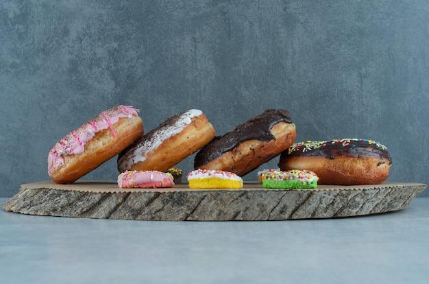 Variedade de donuts em uma placa de madeira no mármore.