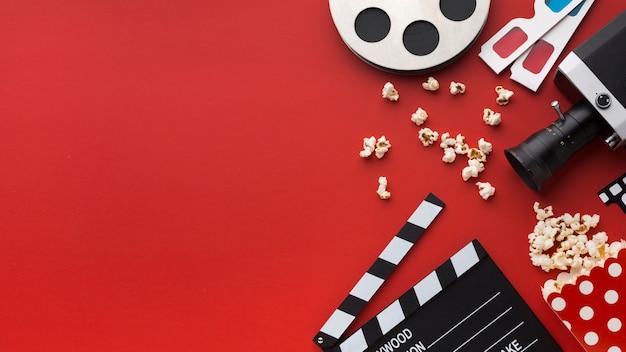 Variedade de elementos de cinema em fundo vermelho, com espaço de cópia