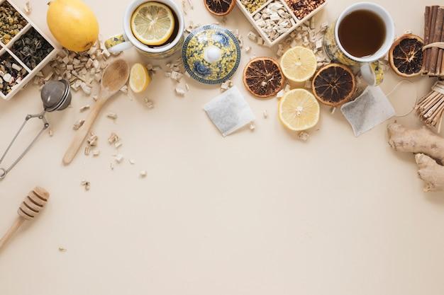 Variedade de ervas; colher; dipper de mel; coador de chá; frutas e ingredientes de uvas secas