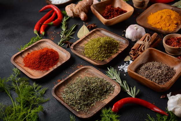 Variedade de especiarias e ervas na mesa da cozinha. várias ervas e especiarias coloridas para cozinhar em fundo escuro
