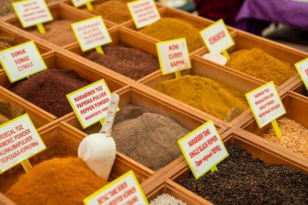 Variedade de especiarias e ervas turcas em tigelas de madeira. especiarias do mercado turco, como açafrão, sumagre e tomilho. cominho, alecrim e isot.