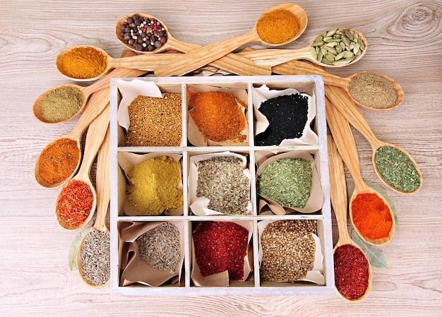 Variedade de especiarias em colheres de madeira e caixa, na mesa de madeira