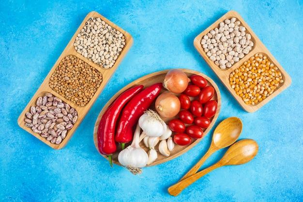 Variedade de especiarias, vegetais e feijão cru sobre fundo azul.