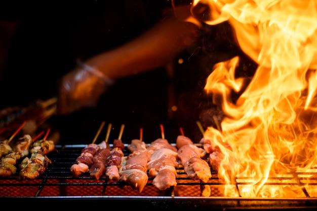 Variedade de espetadas de carne de espetos de churrasco com legumes na grelha flamejante quente