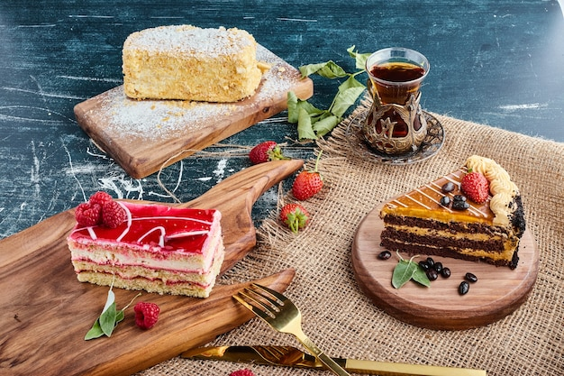 Variedade de fatias de bolo com um copo de chá.