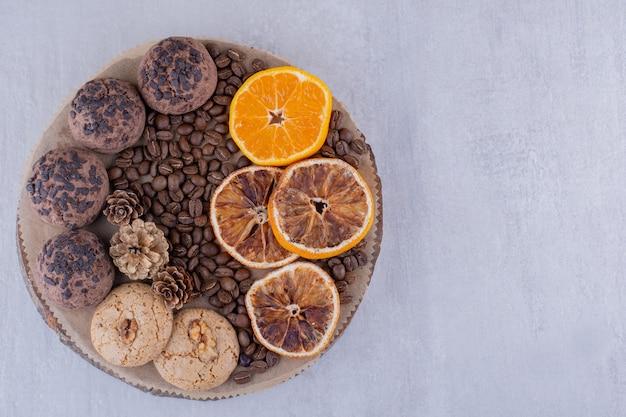 Variedade de fatias de laranja secas e suculentas, grãos de café, pinhas e biscoitos em uma placa sobre fundo branco.