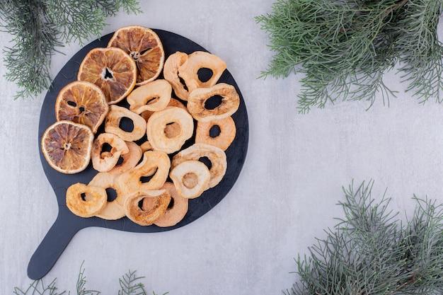 Variedade de fatias de maçã e laranja secas em uma pequena bandeja no fundo branco.