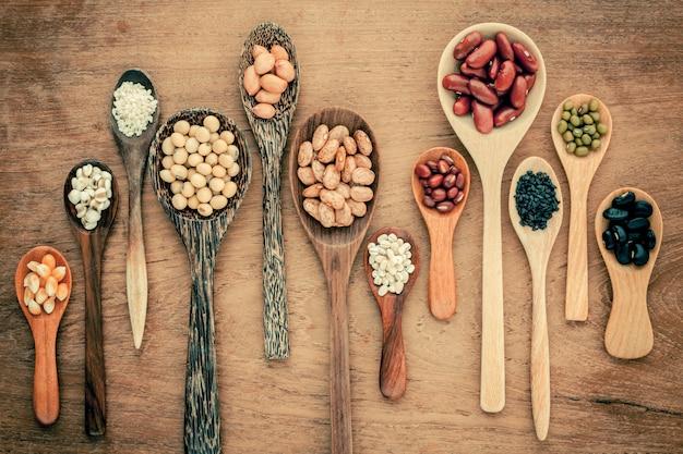 Variedade de feijões e lentilhas no fundo da madeira da teca.