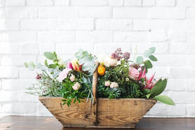 Variedade de flores bonitas em cesta de madeira